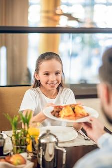 Завтрак с папой. довольно девочка-подросток берет тарелку с едой из рук ее пап