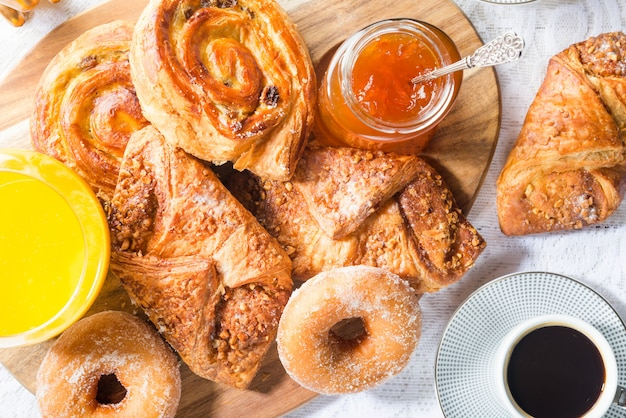 Breakfast with different french pastries, juice and jam