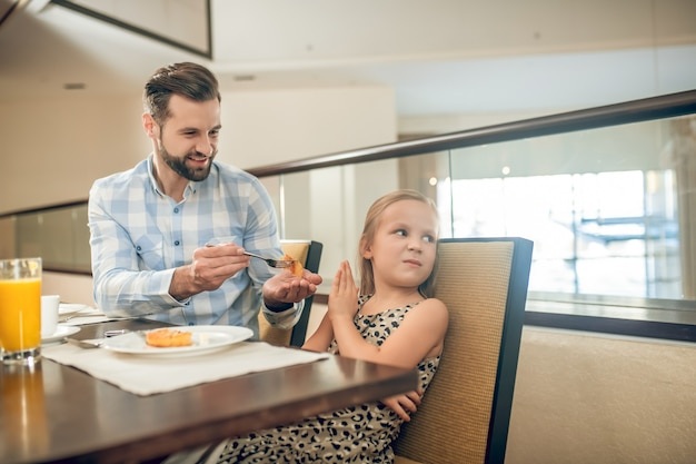 Завтрак с отцом. милая девушка завтракает с папой