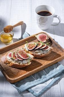 Завтрак с инжиром, сыром и бутербродом с медом на деревянной доске и чашкой кофе на белом столе, солнечное утро