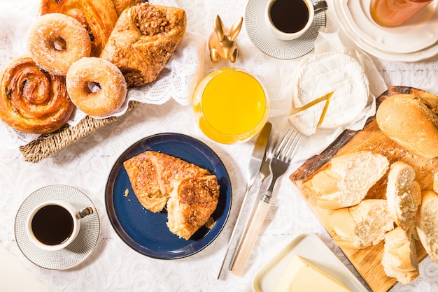 Breakfast with french pastries, bread, cheese and coffee