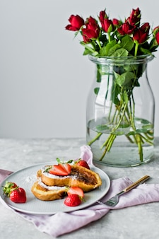 Breakfast with french toast and strawberries, a vase of red roses.