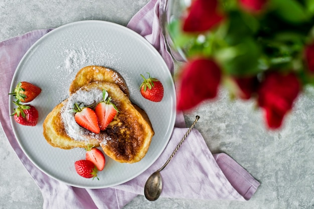 Breakfast with french toast and strawberries, vase with roses.