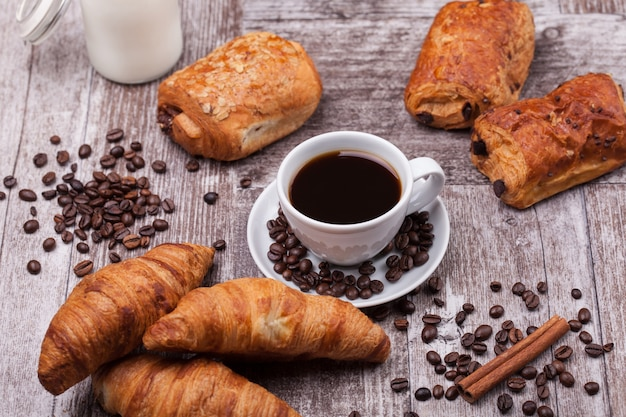 소박한 나무 테이블에 커피와 우유를 곁들인 신선한 코아상으로 구성된 조식. 황금 크루아상.