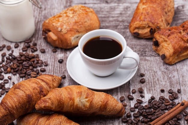 Colazione con coissants freschi con caffè e latte su tavola in legno rustico. cornetto d'oro.