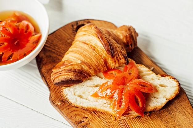 신선한 크루아상과 귤 잼, 과일 조각으로 구성된 조식. 건강한 아침 식사.