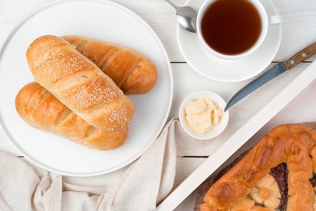 밝은 배경에 신선한 롤과 수제 케이크와 함께 아침 식사.
