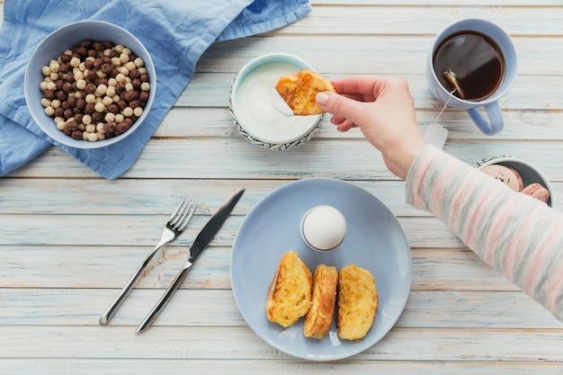 가벼운 나무 표면에 튀긴 크루통, 요구르트, 홍차와 함께 아침 식사. 여름 나라 음식. 평면도