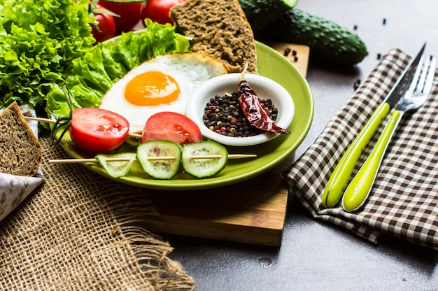 Breakfast with fried egg and vegetables
