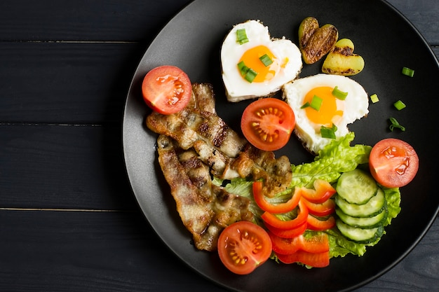 目玉焼き、ベーコン、新鮮な野菜を使った朝食。黒いプレートで、木製の背景に。