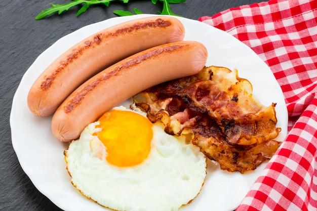 어두운 돌 배경에 계란 프라이, 베이컨, 소시지, 야채 샐러드가 포함된 아침 식사.