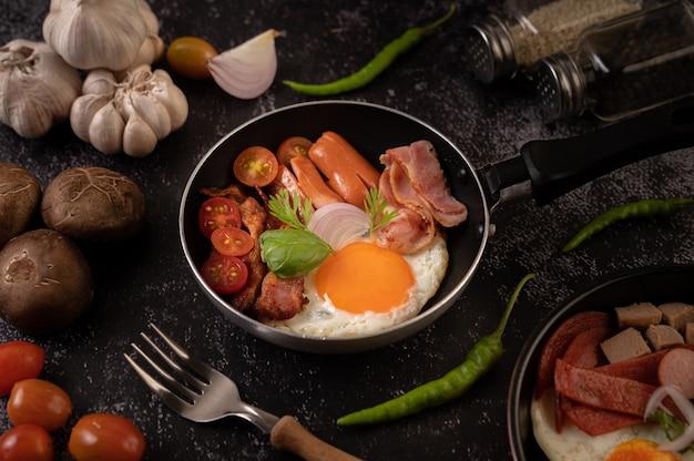 Завтрак с яичницей, колбасой и ветчиной на сковороде с помидорами. чили и базилик