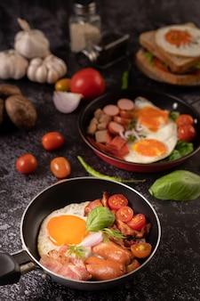 토마토와 함께 냄비에 튀긴 계란, 소시지, 햄으로 아침 식사. 칠리와 바질