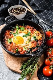 朝食、目玉焼き、トマト。鍋にシャクシュカ。