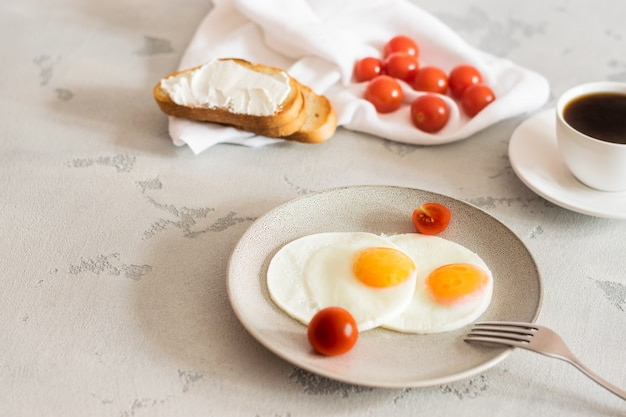 目玉焼き、トマト、トースト、爽快なコーヒーの朝食