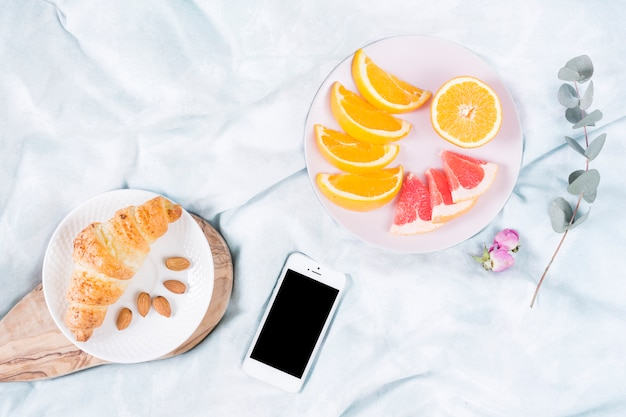 Breakfast with fruits and mobile phone