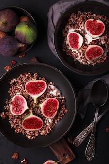 Завтрак с мюсли и инжиром. черные тарелки со свежим и здоровым завтраком. здоровая пища