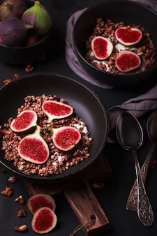 グラノーラとイチジクの朝食。新鮮でヘルシーな朝食付きのブラックプレート。健康食品