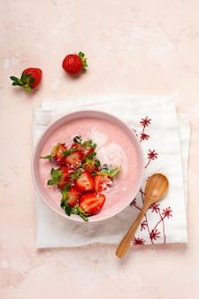 ピンクの明るい背景のボウルにグラノーラ、ココナッツ、イチゴのスムージーと朝食。春のダイエットメニュー。上面図。