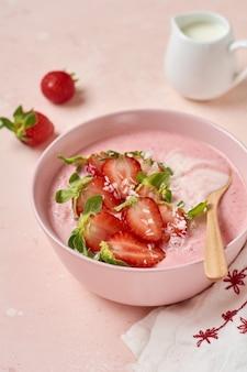 ピンクの明るい背景のボウルにグラノーラ、ココナッツ、イチゴのスムージーと朝食。上面図。