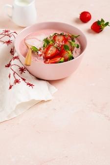 ピンクの明るい壁のボウルにグラノーラ、ココナッツ、イチゴのスムージーを添えて朝食。春のダイエットメニュー。上面図。