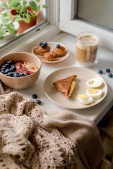 Завтрак с мюсли, яйцами, кофе и пирожными