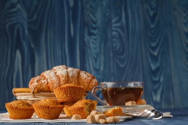 Завтрак с травяным чаем и круассаном на деревянном старинном столе