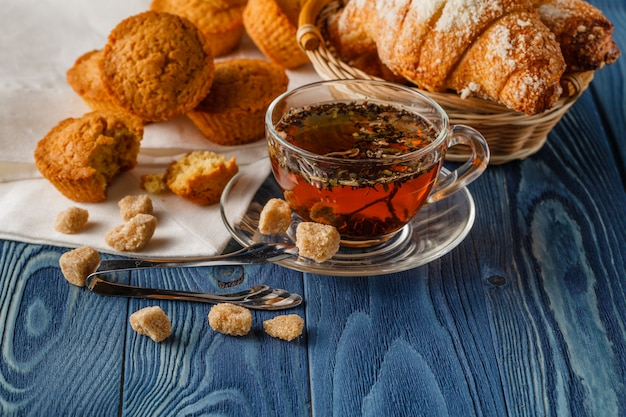 Breakfast with herbal tea and croissant on wooden vintage table