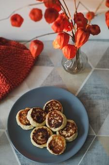 自家製カッテージチーズのパンケーキ、お茶と花瓶をテーブルに置いた朝食