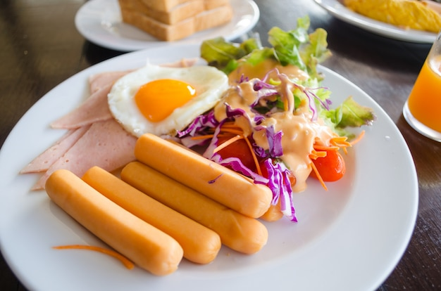 Breakfast with hotdog fried egg and salad