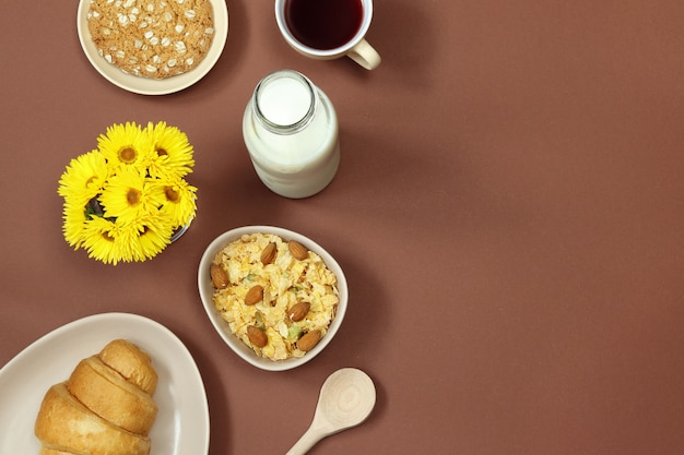 Breakfast with milk, muesli and flowers on brown background