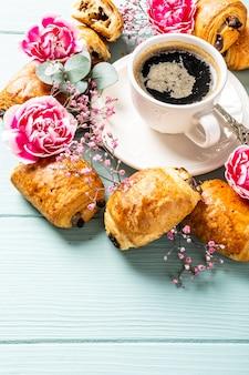 ブルーターコイズの表面にチョコレートとコーヒーカップが入ったミニ焼きたてのクロワッサンパンで朝食。コピースペース