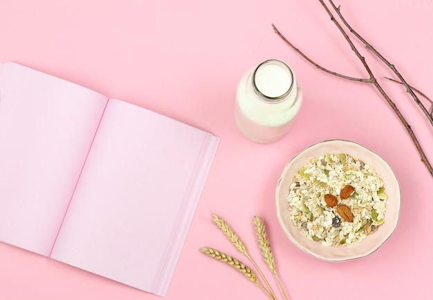 Breakfast with muesli, milk and notes paper on pink background