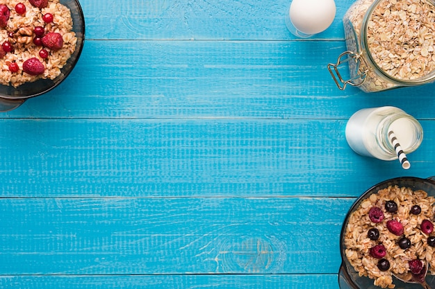 그릇에 오트밀과 딸기, 컵에 우유로 아침 식사. 평면도. 정물. 텍스트를 위한 공간입니다.