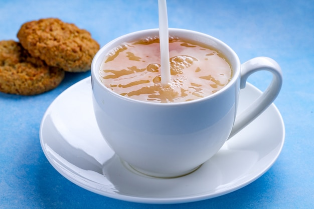 Breakfast with oatmeal cookies and pouring milk into a cup of black tea. flour, cereal dessert and hot drink