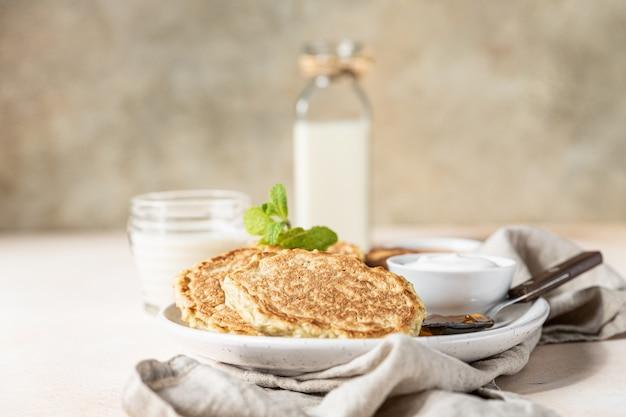 Завтрак с овсяными оладьями с джемом из йогурта и немолочным молоком.