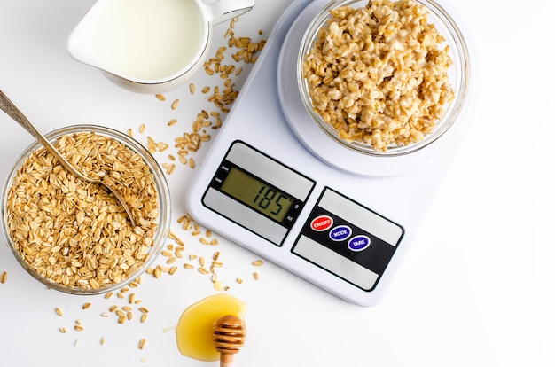 Breakfast with oatmeal porridge on digital kitchen scales, milk and honey on white