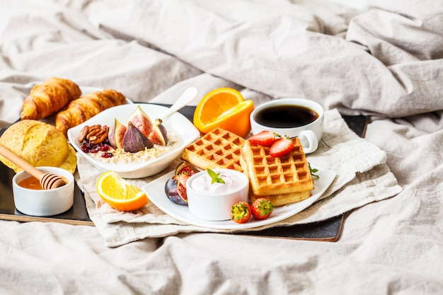 Breakfast with oatmeal, waffles, coffee, croissants and fruits in bed,