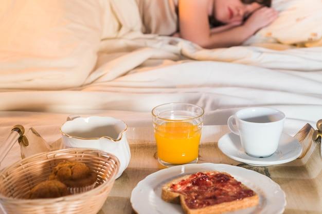 Завтрак с апельсиновым соком, тостами, кофе и кексами в постели девушка спит в постели