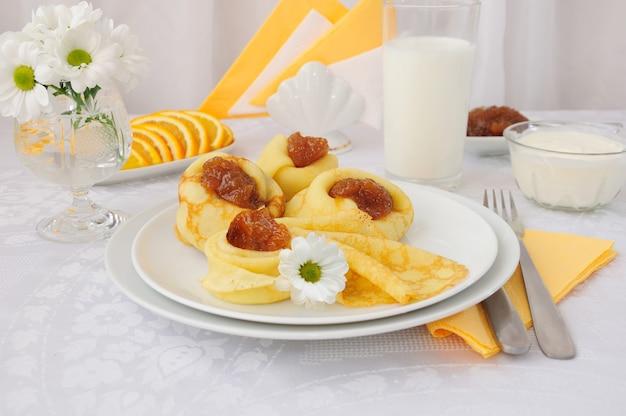 팬케이크, 살구 잼, 우유와 오렌지로 구성된 조식