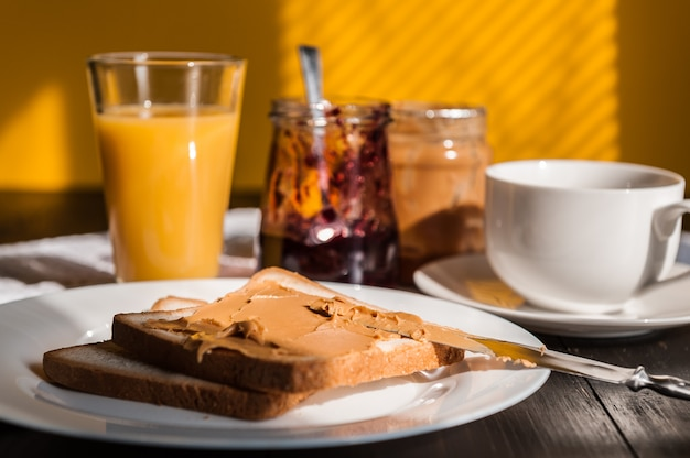 Breakfast with peanut butter and jam and a cup of coffee on a wooden table in the morning sun Premium Photo