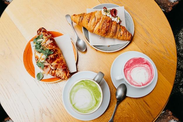 Завтрак с розовым латте, маття кофе и круассанами
