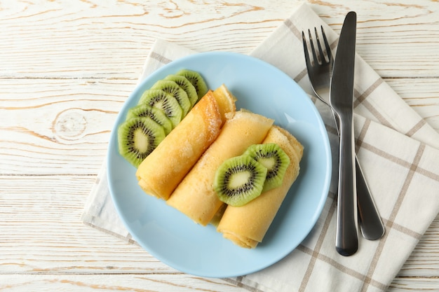 Breakfast with plate of crepes rolls with kiwi slices on wooden table