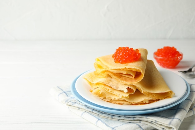 Breakfast with plate of crepes with red caviar on white wooden table
