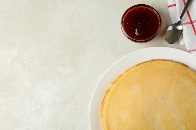 Breakfast with plate of thin pancakes and jam on white textured surface