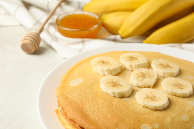 Breakfast with plate of thin pancakes with banana, and jam on white textured surface