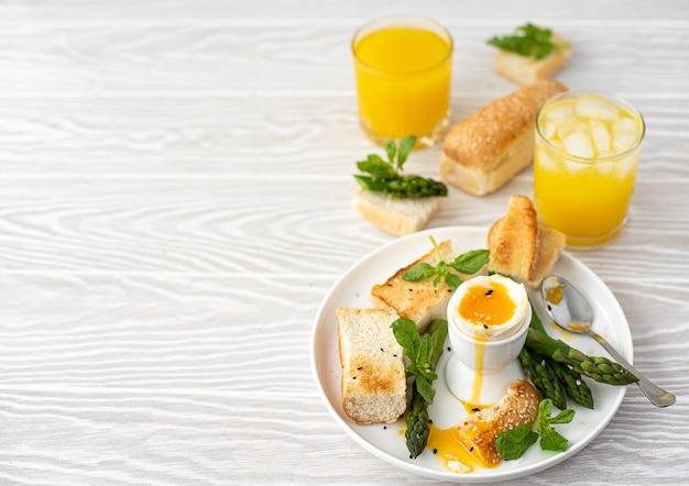 데친 계란, 아스파라거스, 구운 빵으로 아침 식사