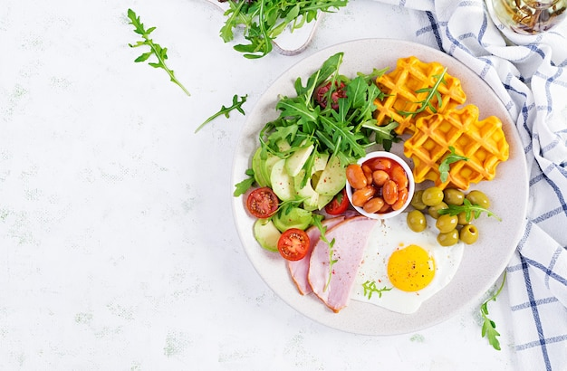 Breakfast with pumpkin waffles, fried egg, ham, tomato, avocado, beans and olives on white surface