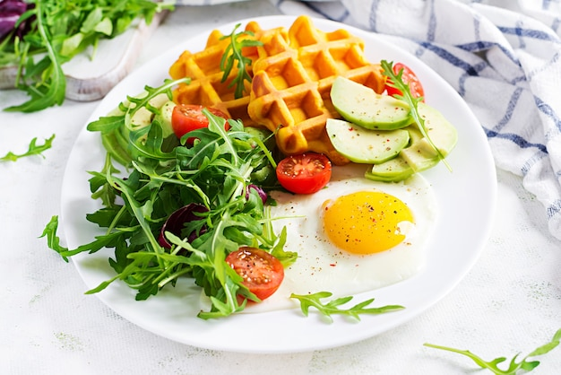 Breakfast with pumpkin waffles, fried egg, tomato, avocado and arugula on white surface