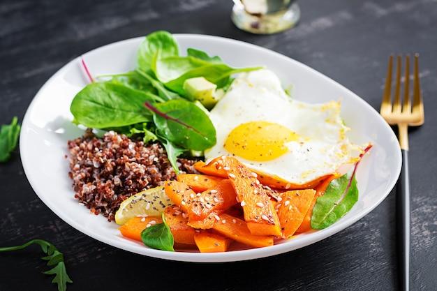 キヌア、スライスしたカボチャ、アボカド、目玉焼きの朝食。ベジタリアン、健康、ダイエット食品のコンセプト。